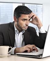 hispanischer Geschäftsmann, der mit gestresstem und besorgtem Computer arbeitet foto