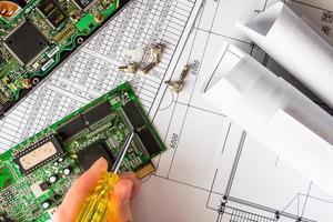 Reparieren Sie einen kaputten Computer, die Hand hält einen Schraubenzieher foto