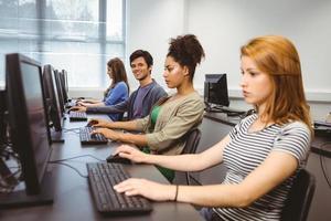 glücklicher Student in der Computerklasse, die in die Kamera lächelt
