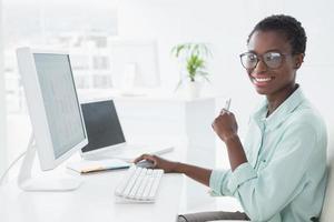 glückliche Geschäftsfrau, die am Schreibtisch arbeitet