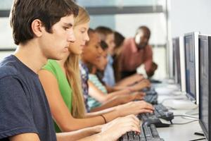 Gruppe von Studenten, die an Computern im Klassenzimmer arbeiten foto
