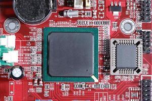 Nahaufnahme der roten elektronischen Leiterplatte mit Prozessor