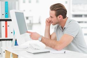 lächelnder Geschäftsmann am Telefon, der seinen Computer zeigt foto