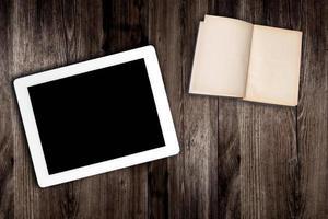 Tablet-Computer und Buch auf alten Holztisch foto