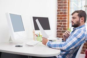 Gelegenheitsgeschäftsmann, der an seinem Schreibtisch arbeitet foto