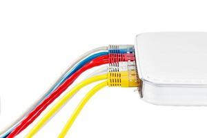 Mehrfarbige Netzwerkkabel, die auf weißem Hintergrund mit dem Router verbunden sind