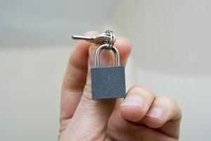 Männerhand mit Schloss und Schlüsseln foto