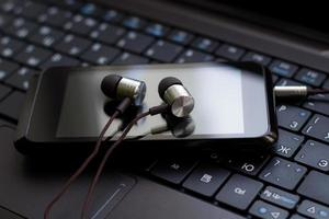 Kopfhörer und Handy an der Tastatur.
