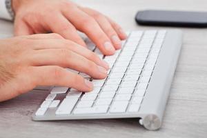 männliche Hand, die auf Tastatur tippt foto