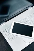 Laptop mit weißem digitalem Tablet auf dem Schreibtisch