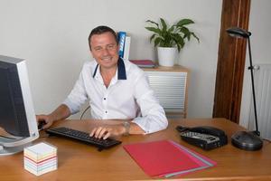 Mann, der im Büro vor Desktop-Computer arbeitet foto