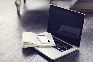 Handy mit offenem Buch und Laptop auf dem Boden