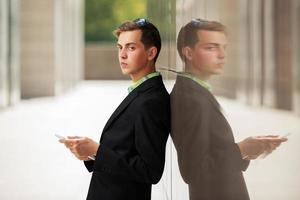 junger Mann mit einem Tablet-Computer an der Wand foto