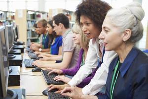 Gruppe reifer Studenten, die mit dem Tutor an Computern arbeiten foto