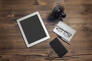 Tablet-Computer, Smartphone, Kaffeetasse, Notizblock und Brille foto