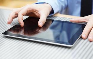 Geschäftsmann, der zwei Finger auf Touchscreen auf Tablet-Computer bewegt foto