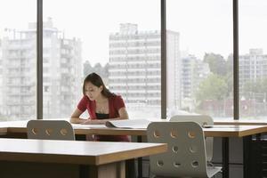Geschäftsfrau liest am Schreibtisch