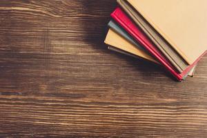 Bücher auf Holzschreibtisch.