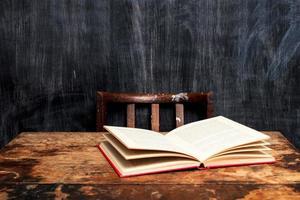 offenes Buch auf dem Schreibtisch an der Tafel foto