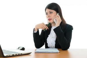 Geschäftsfrau sitzt am Schreibtisch foto