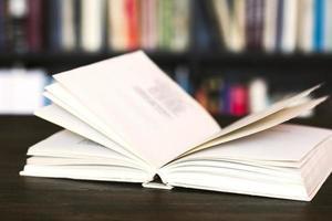 offenes Buch auf Holzschreibtisch.