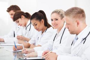 Reihe von Ärzten, die am Schreibtisch schreiben foto