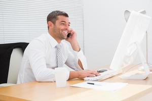 lächelnder Geschäftsmann, der an seinem Schreibtisch anruft foto