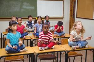 Schüler meditieren in Lotussitz auf dem Schreibtisch foto