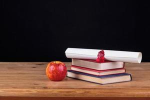 Schulbank mit schwarzem Hintergrund des Diploms