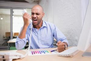 wütender Geschäftsmann, der Telefon am Schreibtisch benutzt
