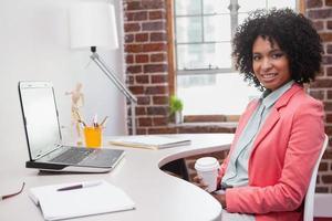 glückliche lässige Geschäftsfrau, die am Schreibtisch sitzt