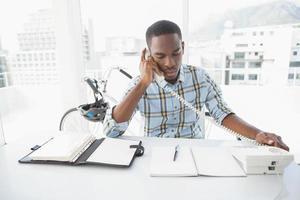 ernsthafter Geschäftsmann, der Schreibtisch-Tagebuch liest und anruft