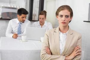 selbstbewusste Geschäftsfrau mit Kollegen am Schreibtisch foto