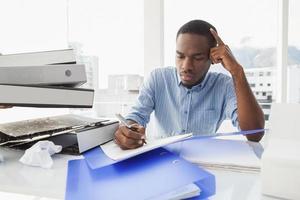müder Geschäftsmann, der Notizen am Schreibtisch schreibt foto