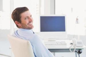 lächelnder Geschäftsmann, der an seinem Schreibtisch sitzt