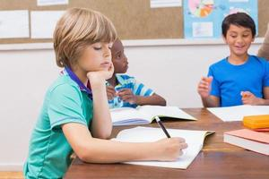 süße Schüler schreiben am Schreibtisch im Klassenzimmer foto