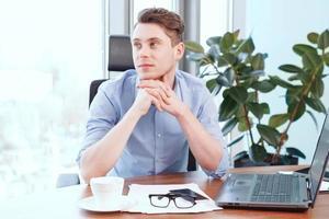 junger Mann, der am Schreibtisch im Büro sitzt foto