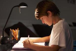 Junge, der am Schreibtisch im Schlafzimmer studiert foto