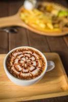 Latte Kaffeekunst auf dem Holzschreibtisch