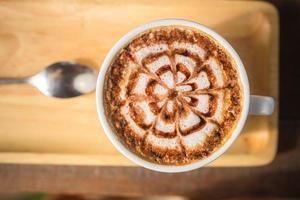 Latte Kaffeekunst auf dem Holzschreibtisch foto