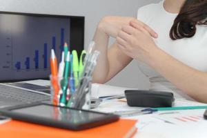 junge Geschäftsfrau, die Stift von ihrem Schreibtisch nimmt foto