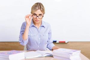 streng aussehender Lehrer sitzt am Schreibtisch