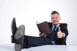 Geschäftsmann liest mit Füßen auf dem Schreibtisch foto