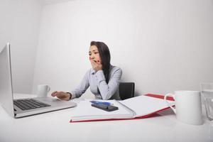schläfrige Geschäftsfrau, die am Laptop am Schreibtisch arbeitet foto