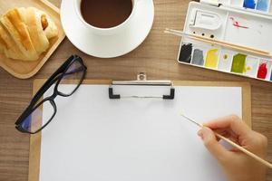 Schreibtisch, der an einem Holztisch arbeitet foto