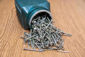 Schachtel mit Schrauben offen auf hölzernem Schreibtischhintergrund foto