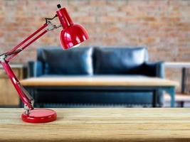Lampe auf Holztischplatte mit verschwommenem Hintergrund des Wohnzimmers foto