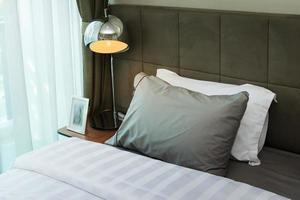 Schreibtischlampe aus Metall und graues Kissen auf dem Bett