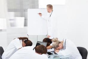Arzt, der Kollegen vorstellt, die am Schreibtisch schlafen foto