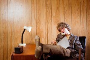 fauler Retro-Büroangestellter mit Füßen auf Schreibtisch foto